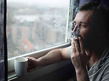 Man smoking cigarette by window ledge